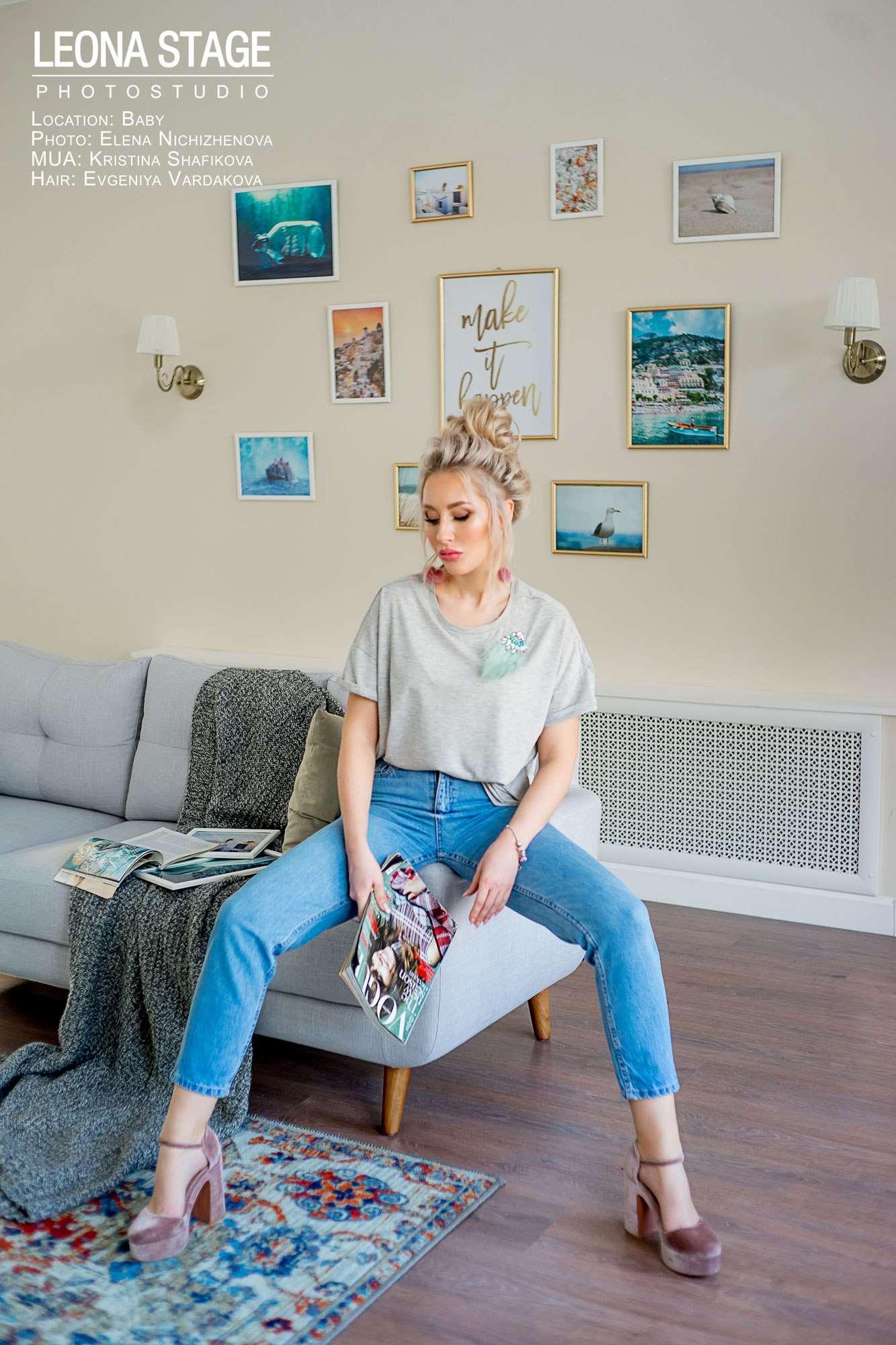 девушка в голубых джинсах позирует на диване